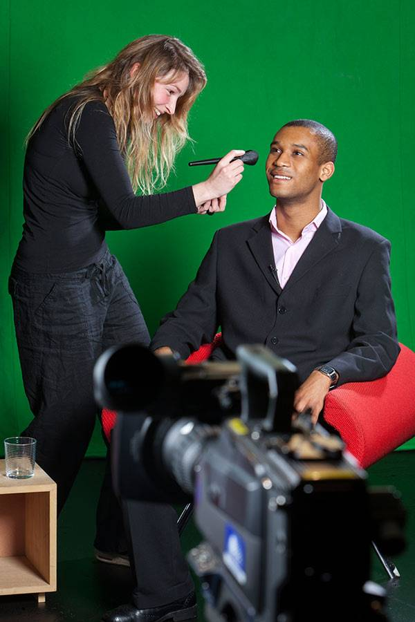 Woman applying makeup to man