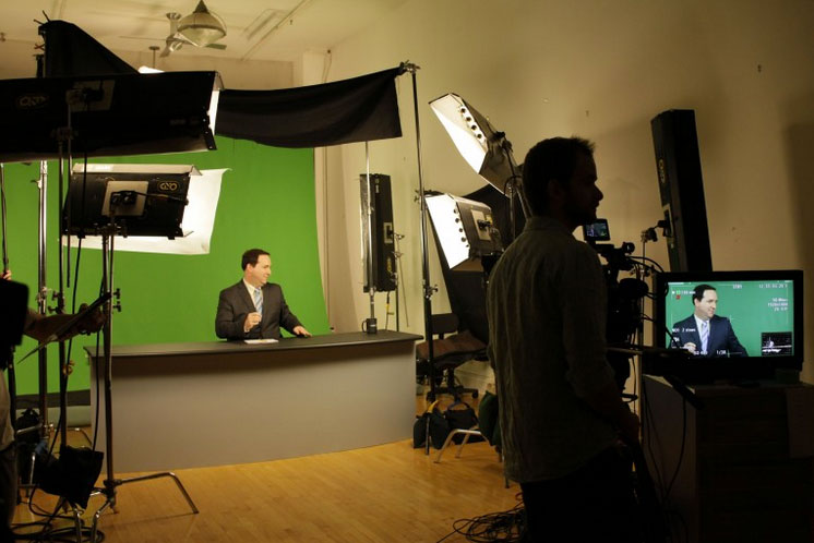 man at desk in front of green screen making an infomerical