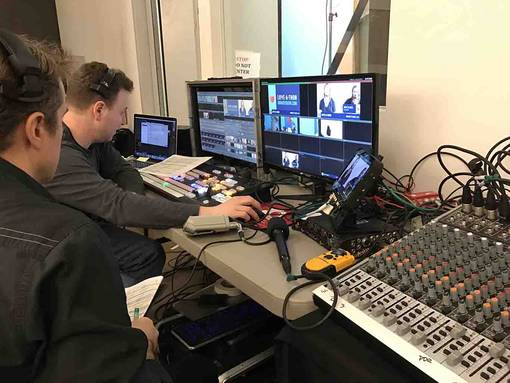 Two operators in front of WebCasting equipment in studio