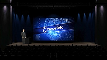 NEWTEK on blue background - man standing on the left