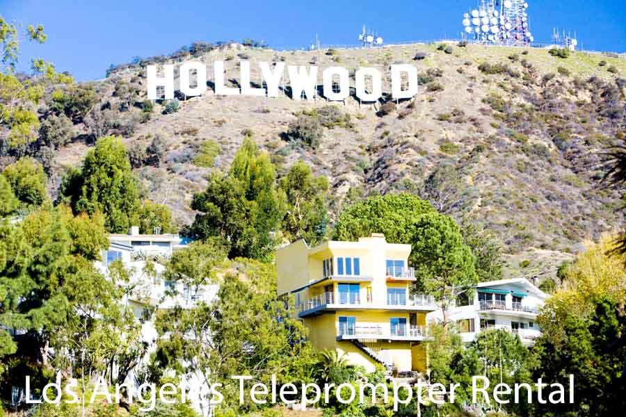 shot of Hollywood hills with sign above and houses on the cliff below