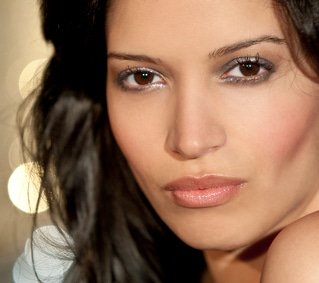 AJ Perez, beautiful Latina headshot. Looks into the camera. Gold BG