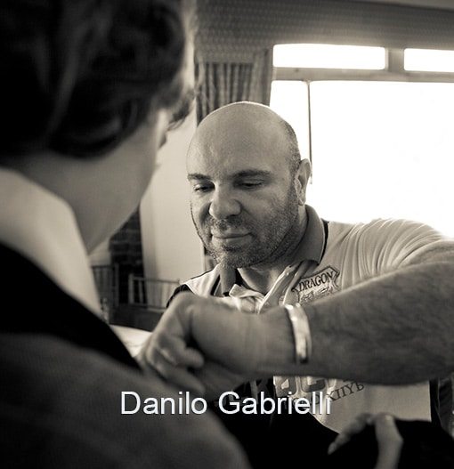 Danilo Headshot Famous fashion Designer adjusts garment of male model