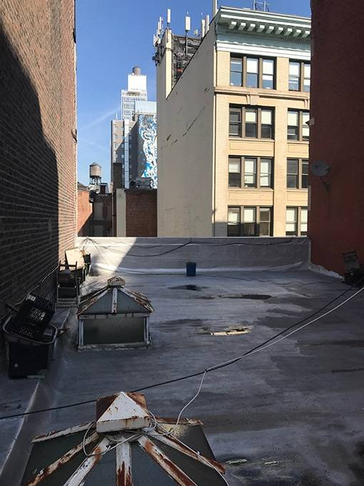Roof of NYC building with large yellow building in the background