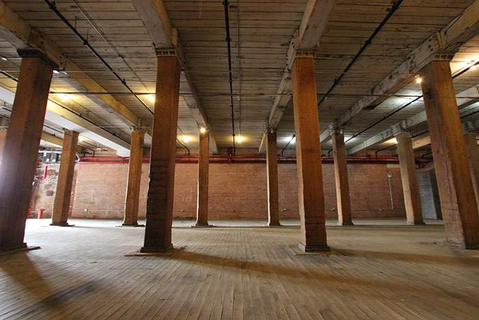 Warehouse Unit 522 large empty warehouse with high windows sunlight large emprt space with wooden columns brick wall