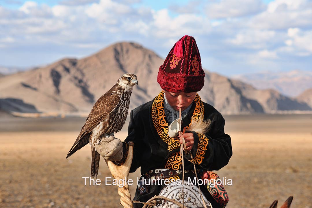 A young Mongolian The Eagle Huntress sits on her horse with an eagle on her arm