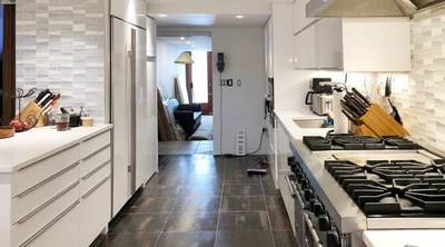 Tribeca studio and loft kitchen . with all white appliances left and right (green Screen Sound Stage Rental NYC)