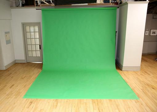 Green Screen Studio - large green screen draped to the wooden floor - door and white column in the back