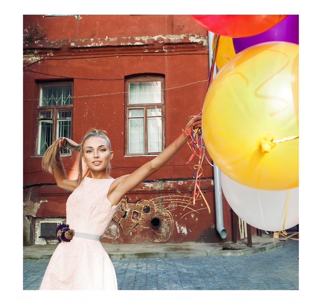 Teenage Girl holding balloons for sweet 16,