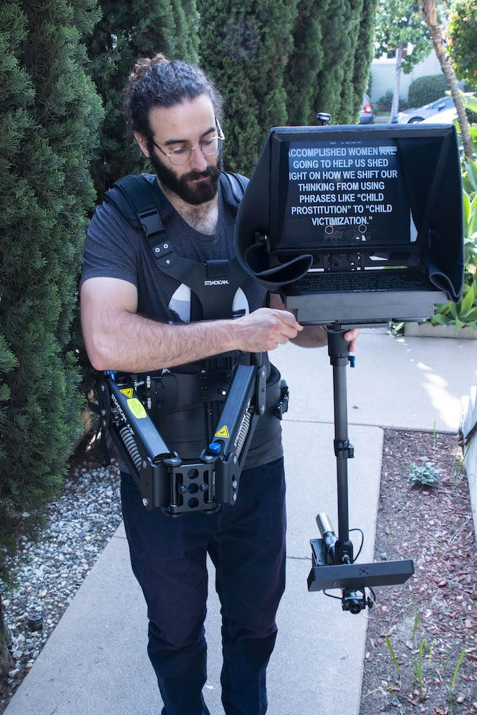 Teleprompter Rental: SteadiCam Prompter with Operator, bearded man dressed in black holding the unit - outside