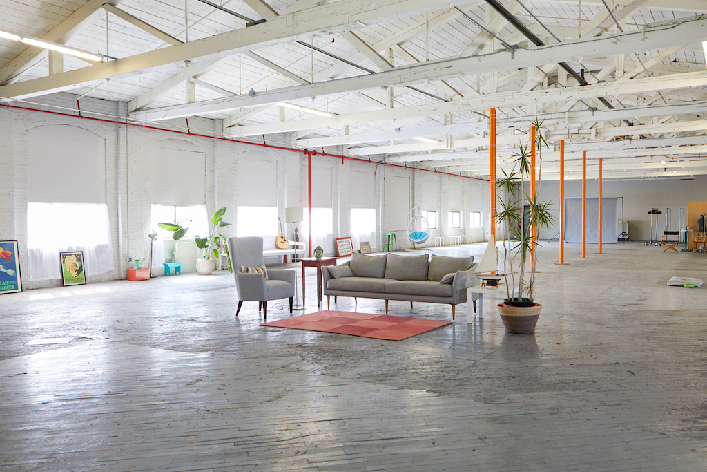 Spacious loft space with orange columns, grey sofa and chairs, orange rug