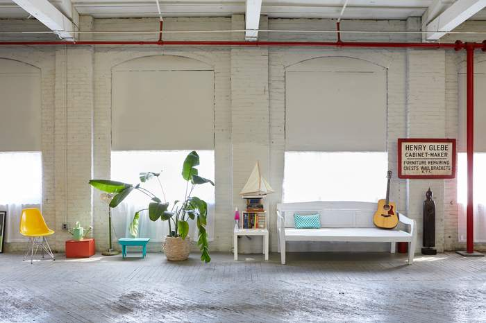 Loft space with furniture, plants, a guitar and large windows