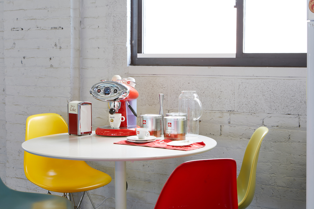 Studio - white table, coffee maker, table set-up, glasses, chairs, one red one white