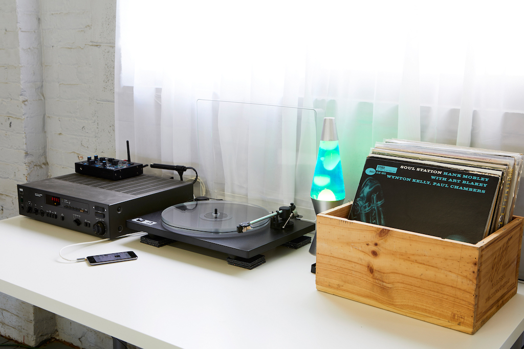 Record player and box with albims and lava lamp on desk