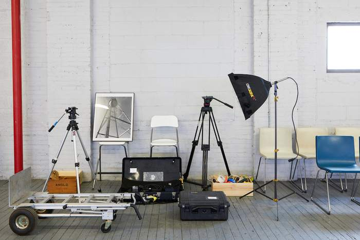 Studio Rental Equipment, tripods, lights and cables arranged together in front of a gray wall.
