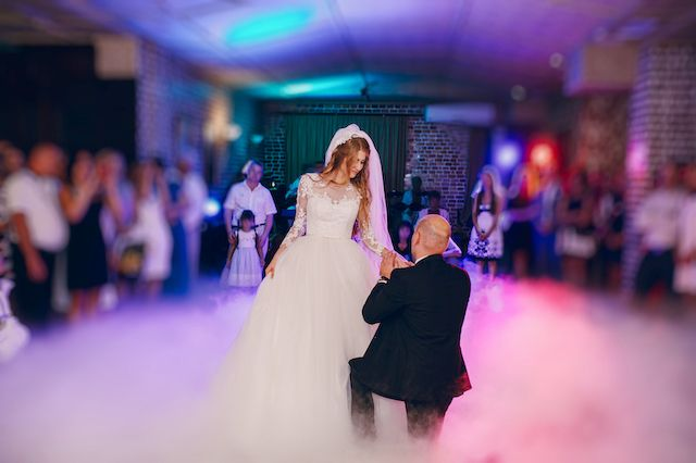 Wedding - groom kneels before his bride - Guests look on in background (soft focus) WebCasting of happy event.