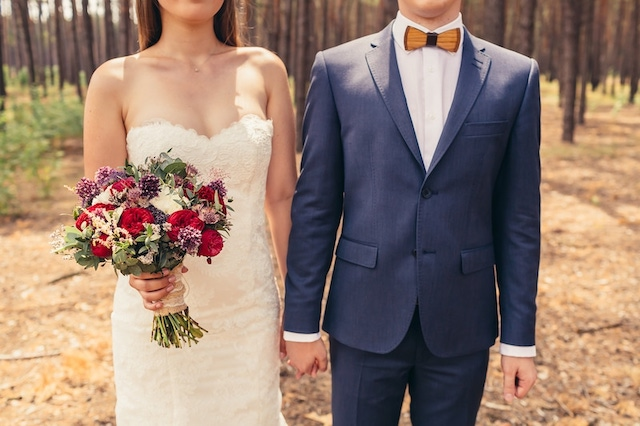 Cropped picture of bride holding bouquet and holding hands with groom in a forest background.