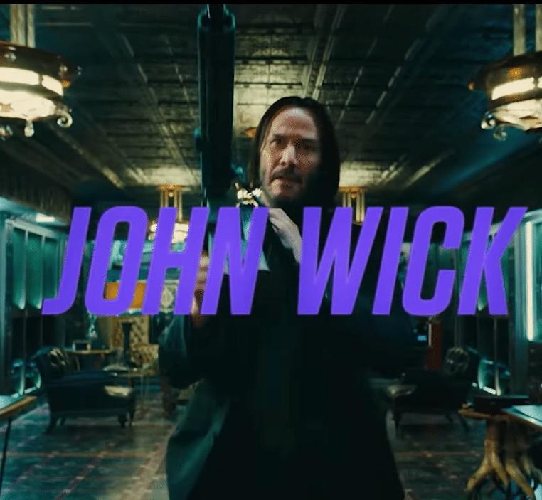 John Wick Video Trailer Screenshot, Keanu Reeves walking toward with gun, John Wick Text in purple over the image