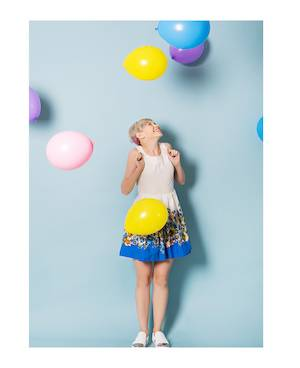 Young girl seems happy - looks at balloons above her head.