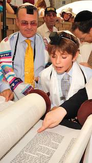 Young boy pointing to Scroll - adults looking on.  Bar Mitzvah.