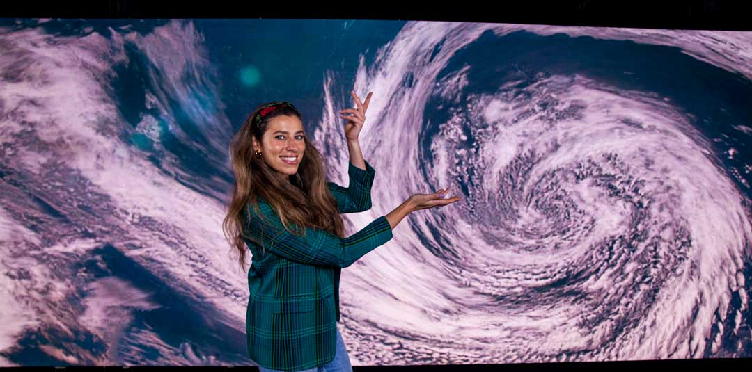 Leah in fornt of LED video wall displaying a storm